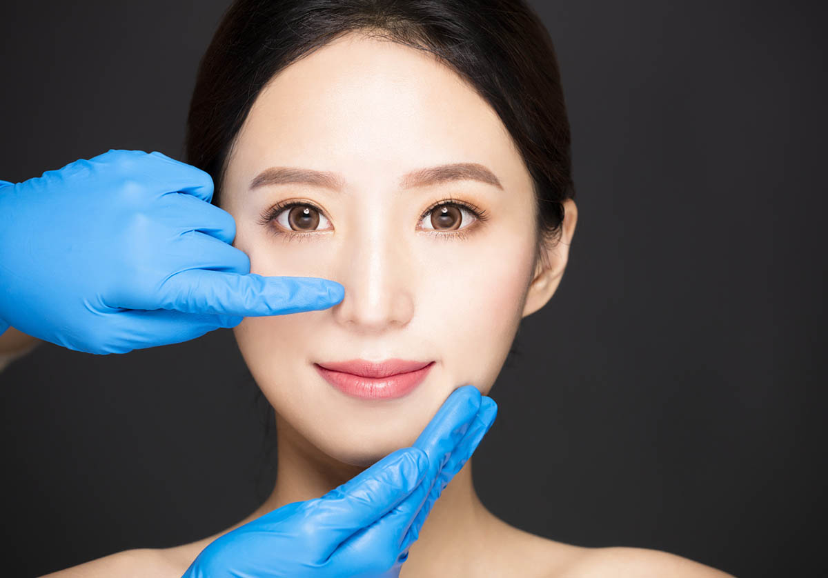 aesthetic doctor examining female patient nose