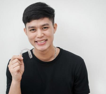 Invisalign teeth boy holding braces