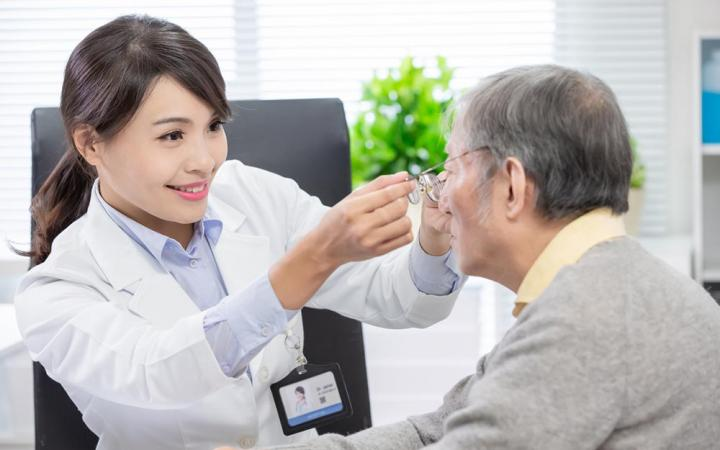 Ophthalmologists checking old man's eyes
