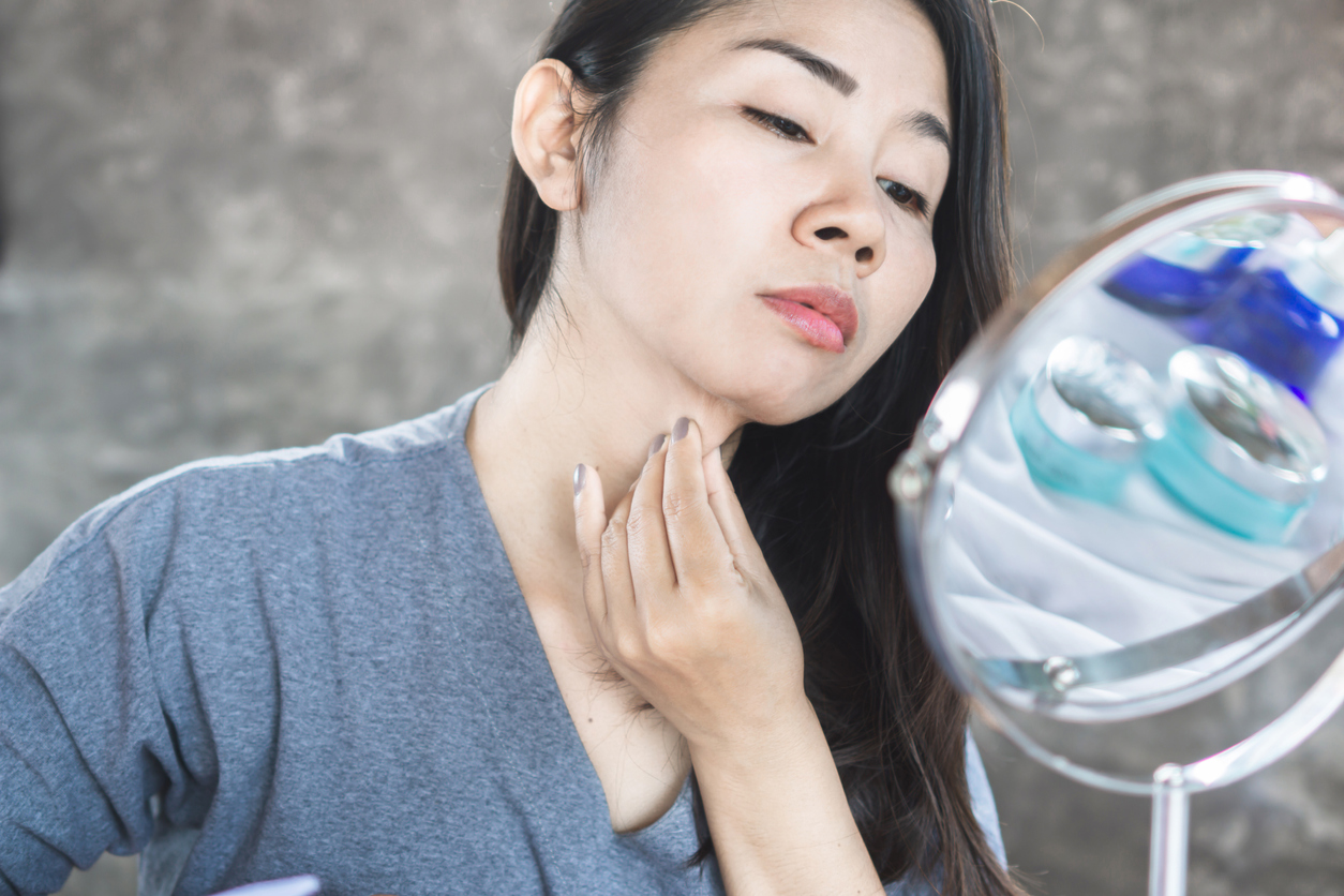 asian woman looking at her double chin in mirror