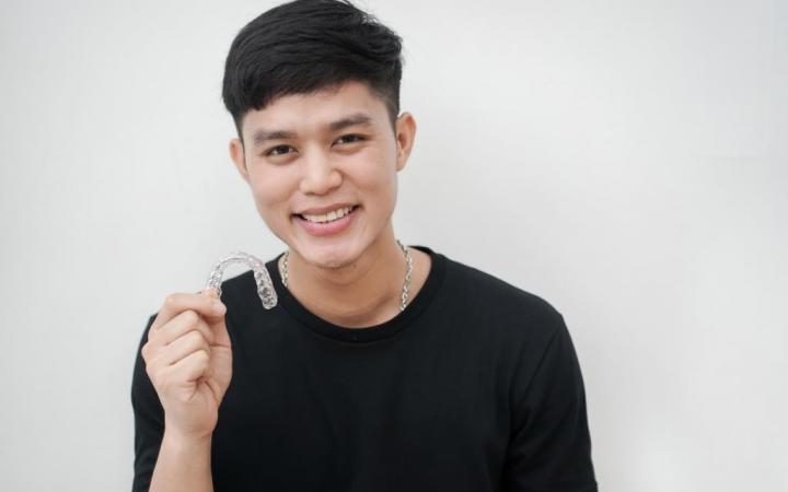 Invisalign teeth boy holding braces