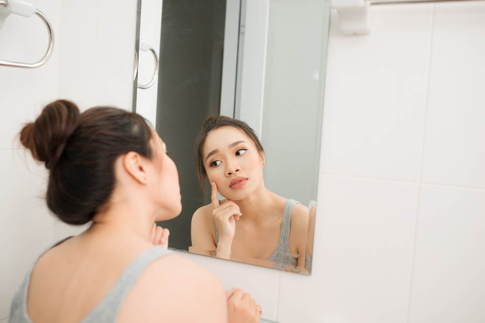 Beautiful woman looking at the mirror